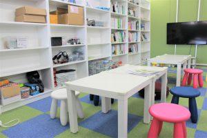 教室風景の写真です。参考書が置かれている棚の前にひざ下くらいのテーブルがあり、白・ピンク・青の可愛らしい椅子が並んでいます。