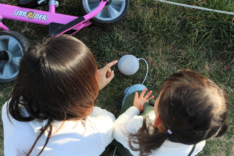 Google Home Miniを外で娘と使っている写真