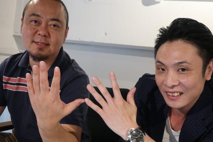 2人がマイクロチップを入れた手でポーズする画像