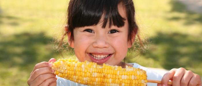 トウモロコシを美味しそうに食べている女の子